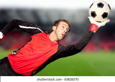Football goalkeeper at a stadium catching the ball