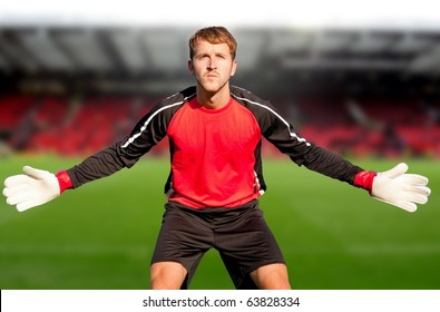 Football goalkeeper at the stadium ready to catch a ball