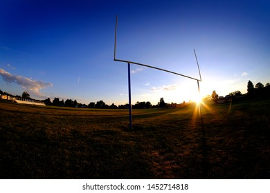 Football goalposts goal posts uprights at sunset with sun sky and bleachers