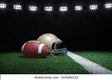 Football and gold helmet on grass field below stadium lights at night