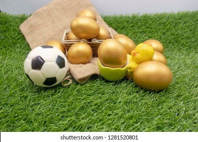 Football with golden eggs are on green grass