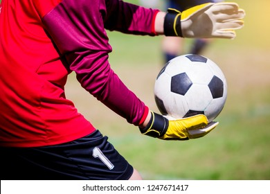 Football in hand of goalkeeper.  Soccer player training or football match.