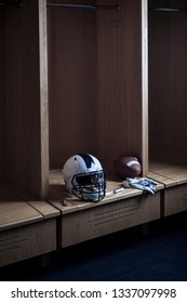 Football and a helmet sitting in locker room in a sports stadium. Spotlight showing the individual locker ready for game day.