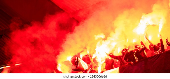 football hooligans with mask holding torches in fire while supporting their favorite team during a match at stadium