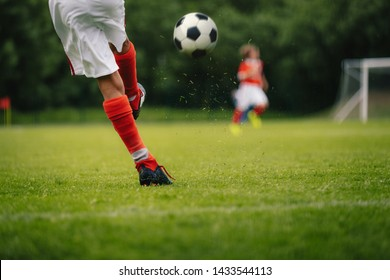 Football Kick. Youth Player Kicking Soccer Ball on Field. Football Ball in Motion. Legs of Sports Soccer Football Player Sportsman In Motion With Ball