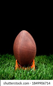 A football kickoff on a grass field with a black background to represent nighttime.