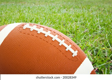 Football laying on a field of grass with room for text.