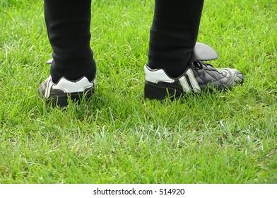 Football legs on green grass