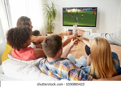 football, leisure and people concept - happy friends clinking beer bottles and watching soccer game on tv at home