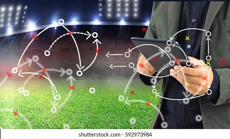 Football manager planning tactic with soccer field and bright spotlights.