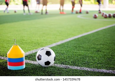 football and marker cones on green artificial turf with blurry soccer team training, blurry kid soccer player jogging between marker cones and control ball with soccer equipment in soccer academy.