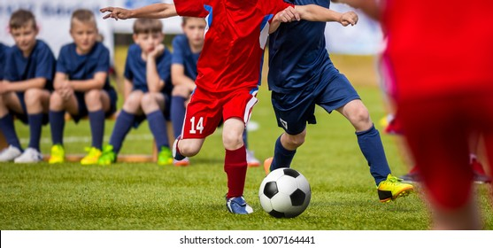 Football match for young players. Training and football soccer tournament for children. Youth soccer competition betweeen two footballers. Red team versus blue team