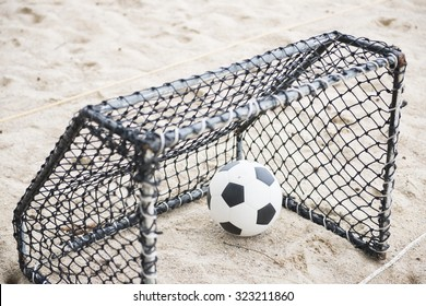 football in the mini goal on the sand, sport