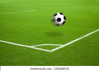 Football in motion on soccer court with white stripes corner markings. Saturated green grass and football in the air with motion blur and cast shadow.