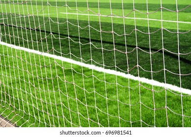 Football net on goal behind back view on field