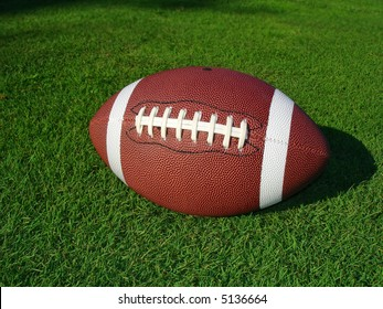 Football on short grass, side angle.
