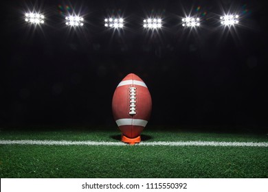 A football on a tee on a yard line under lights at night