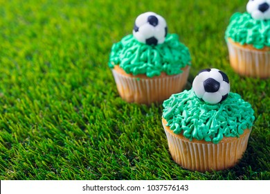 Football party, birthday decorated cupcake on green grass background. Copy space.