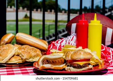 Football party with cheeseburger, hot dog, potato chips, pom poms, buns, and football.  Football field in background.