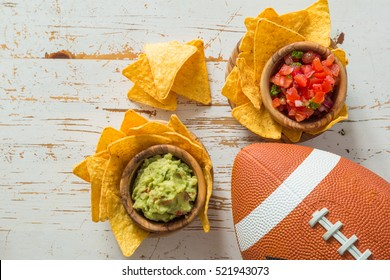 Football party food, super bowl day, nachos salsa guacamole, top view  on wood background