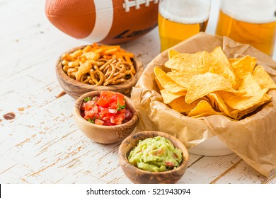 Football party food, super bowl day, nachos salsa guacamole on wood background