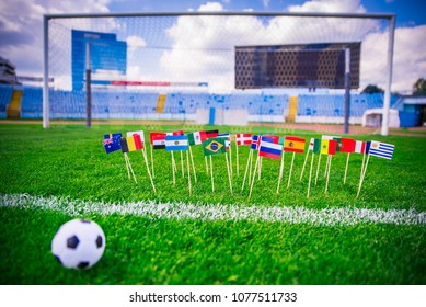Football pitch, all world nations flags, blue sky, football net in background. Sport photo, edit space.