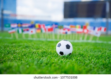 Football pitch, world nations flags, blue sky, football net in background. Sport photo, edit space..