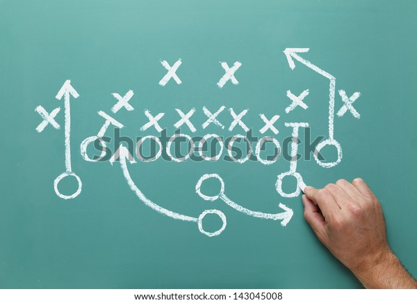 Football play drawn on Green Chalk Board with Hand.