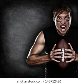 Football player aggressive portrait holding american football on black blackboard background with copy space for text or design. Caucasian male model in his 20s.