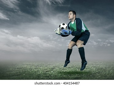 Football player with ball in action under sky with clouds