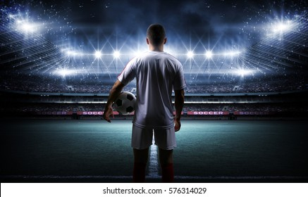 Football player with ball on field of stadium - Shutterstock ID 576314029