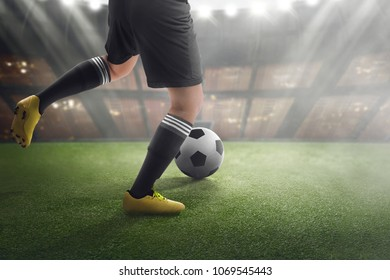 Football player with ball on the match at stadium field