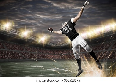 Football Player with a black uniform catching a ball on a stadium.