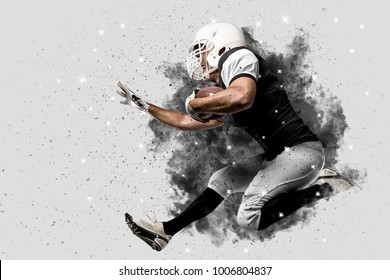 Football Player with a black uniform coming out of a blast of smoke running.