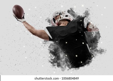 Football Player with a black uniform coming out of a blast of smoke, catching a ball.