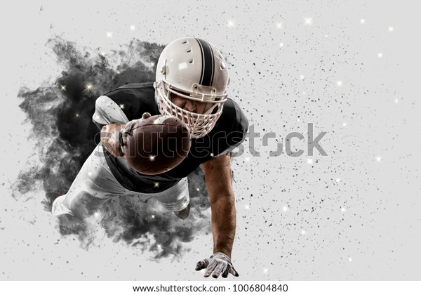 Football Player with a black uniform coming out of a blast of smoke.