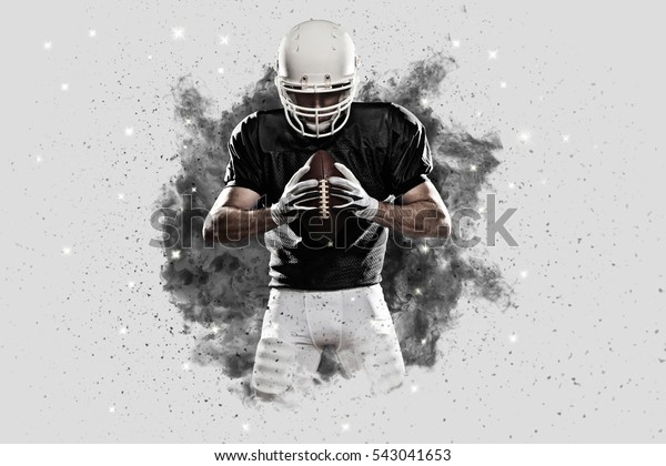 Football Player with a black uniform coming out of a blast of smoke .