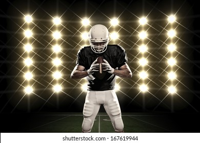 Football Player with a black uniform in front of lights