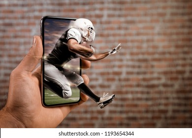 Football Player with a black uniform playing and coming out of a full screen phone in front of a brick wall. Watching a football game on demand concept. copy space.