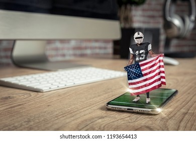 Football Player with a black uniform playing and coming out of a full screen phone on a wooden table. Watching a football game on demand concept. copy space.
