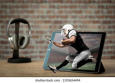 Football Player with a black uniform playing and coming out of a tablet. Watching a football game on demand concept.