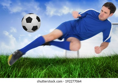 Football player in blue kicking the ball against field of grass under blue sky