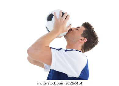 Football player in blue kissing the ball on white background