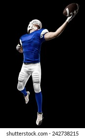 Football Player with a blue uniform making a catching on a black background.