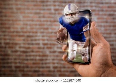 Football Player with a blue uniform playing and coming out of a full screen phone in front of a brick wall. Watching a football game on demand concept. copy space.