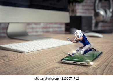 Football Player with a blue uniform playing and coming out of a full screen phone on a wooden table. Watching a football game on demand concept. copy space.