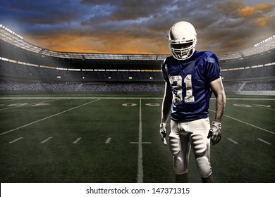 Football player with a blue uniform, in a stadium with fans wearing blue uniform