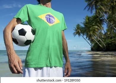 Football player in Brazilian flag t-shirt holding soccer ball on remote beach in Nordeste Bahia Brazil