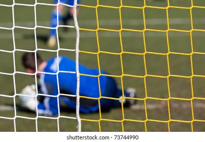 Football player catching the ball in a goal net with grass background