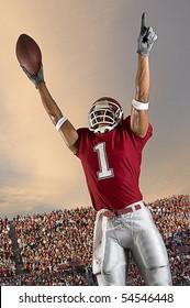 Football player celebrates after scoring a touchdown. Vertical shot.
